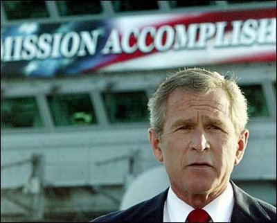 "George Bush in front of a banner that reads ""Mission Accomplished"""