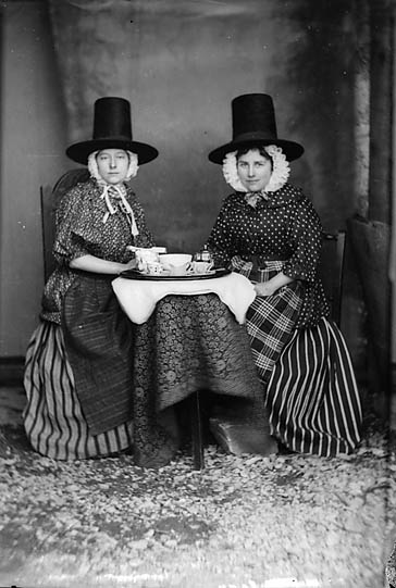 Two_women_in_national_dress_drinking_tea_(Jones)_NLW3363089
